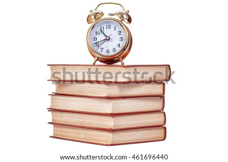 Golden alarm clock standing on books isolated on a white background