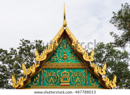 golden ancient texture on emerald wall in front of temple roof.