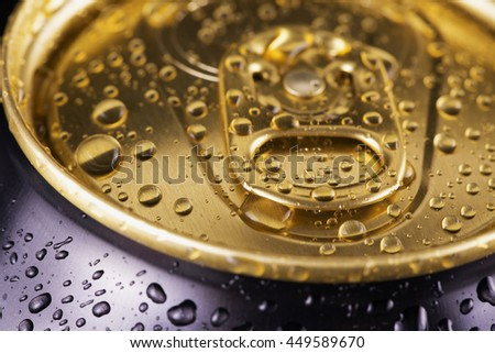 Golden and black can with drops of water, strict close up, horizontal image - stock photo