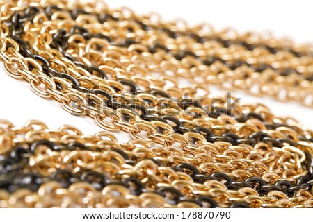 Golden and black chains, closeup on the white background