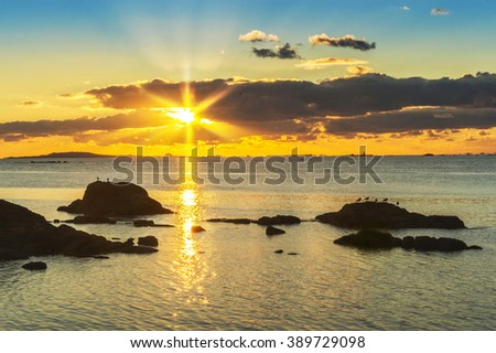 Golden and cloudy sunset in Illa de Arousa with Salvora Island at background and starry sun rising between the golden clouds - stock photo