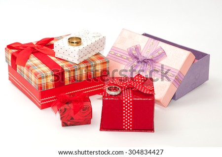 Golden and diamond ring and bunch of gift box with bows.