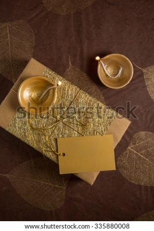 Golden and glittering Indian festive gift pack and traditional lamps. View from top. - stock photo
