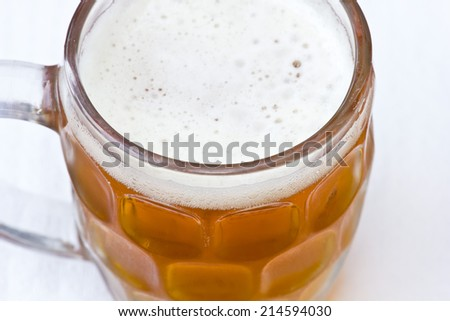 Golden and orange beer with little foam on a glass jar close up still from a top point of view.