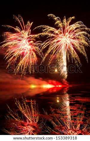 Golden and Purple Fireworks reflected in a murky lake - stock photo