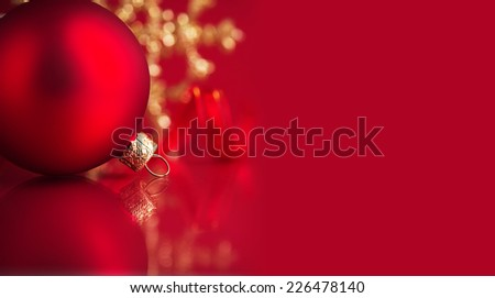 Golden and red christmas ornaments on red background with copy space. Merry christmas card. Winter holidays. Xmas theme. - stock photo