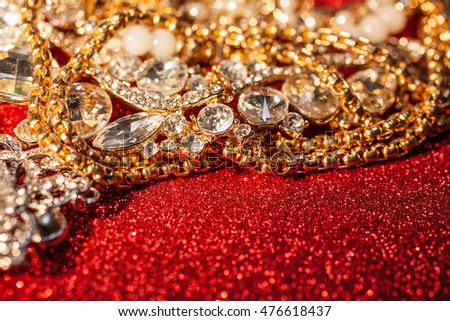 Golden and silver jewelry on red shiny glitter background