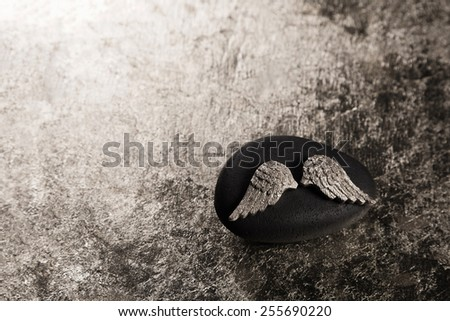 Golden angel wings on a background for mourning or bereavement. - stock photo
