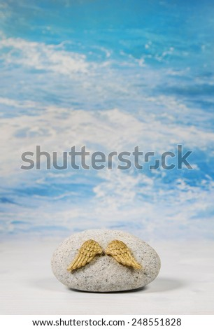 Golden angel wings with stone on blue heaven background for spiritual concepts. - stock photo