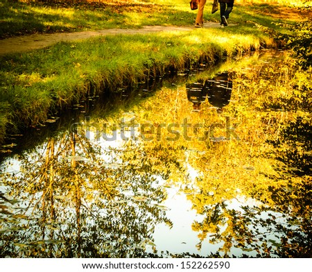 Golden autumn in park. Reflection of trees and walking couple in water.  - stock photo