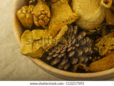 Golden autumnal pot pourri with pine cones, flowers and mushrooms in a wooden cup