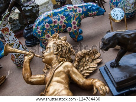 Golden baby angel playing on trumpet. Colorful bear figurine at background. Flea market in Paris. Retro style postcard. - stock photo