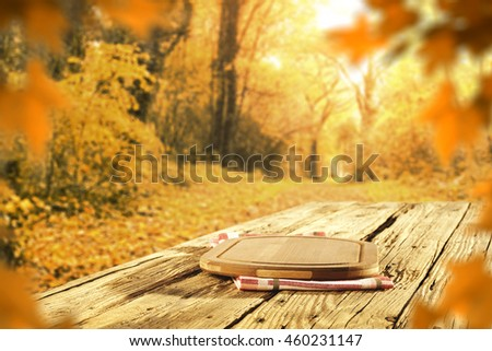 golden background of fall and table of wood and kitchen board and leaves