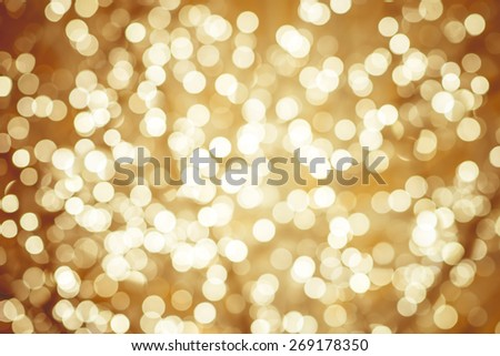 Golden background with natural bokeh defocused sparkling lights. Colorful metallic texture with twinkling lights. Bright and vivid colors - stock photo