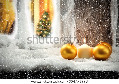 golden balls and snow on window sill  - stock photo