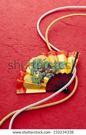 golden beautiful fan and string,on red japanese paper