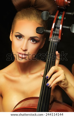 golden beautiful female musician playing a cello.