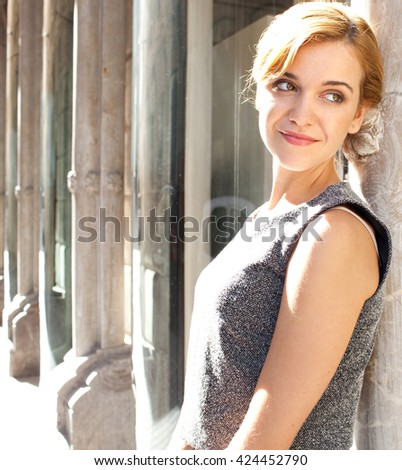Golden beauty portrait of a smart and stylish elegant young woman leaning on a decorative building in a sunny city, relaxing and looking away, outdoors. Healthy woman lifestyle, classic exterior.