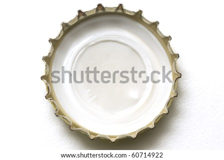 Golden beer cap macro over white background - stock photo