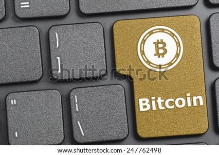 Golden bitcoin key on keyboard - stock photo