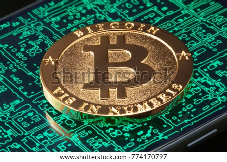 Golden bitcoin on the smartphone screen with abstract digital background.