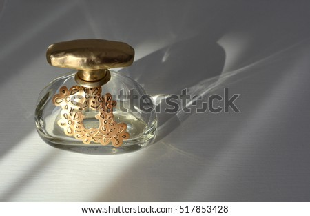 Golden bottle of perfume spraying isolated on white background, perfume bottle isolated. Perfume spray or fragrance bottle in light shining in from a window