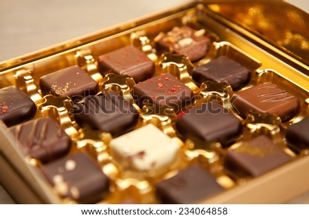 Golden box of fine handmade chocolates in different colors and kinds. - stock photo