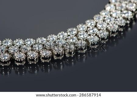 golden bracelet with precious stones on grey background - stock photo