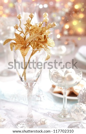 Golden branch on Christmas table. Place setting in white and golden tone. - stock photo