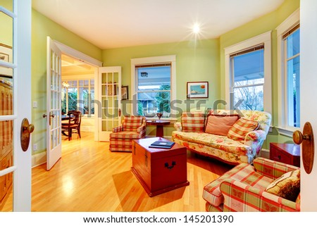 Golden bright green luxury living room with red sofas. - stock photo