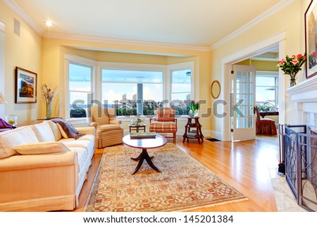 Golden bright yellow luxury living room with fireplace, sofa and rug. - stock photo