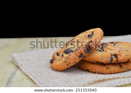 Golden brown, chocolate chip cookies over wooden table. Shallow depth of field. - stock photo