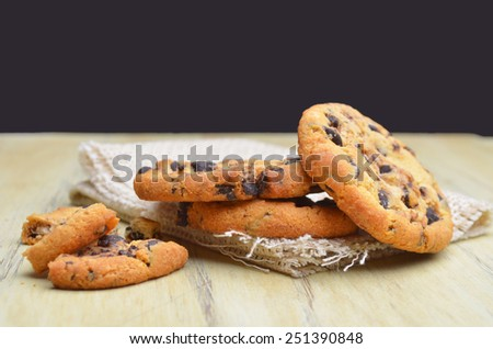 Golden brown, chocolate chip cookies over wooden table. Shallow depth of field.