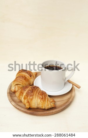 Golden brown croissant and black coffee on wooden plate with space on background
