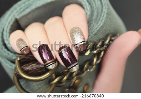 Golden brown French manicure with black stripes on the background of the accessory. - stock photo