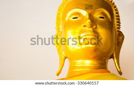 Golden Buddha face in candlelight