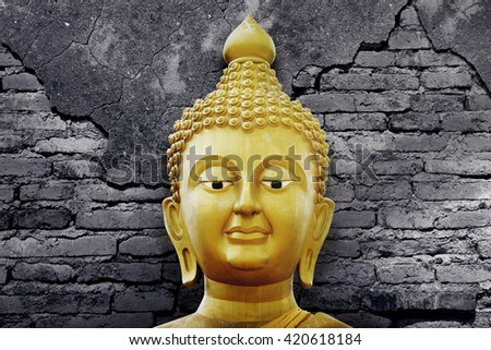 Golden Buddha Face on Black and White Wall Background - stock photo