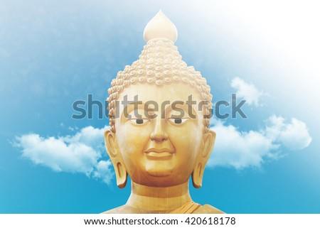 Golden Buddha Face on Blue Sky Background - stock photo