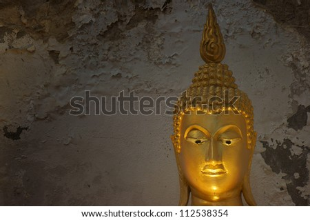 golden buddha face with ancient wall background.