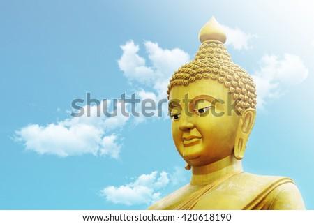 Golden Buddha Portrait / Golden Buddha Face on Blue Sky Background - stock photo