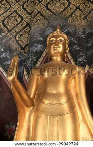 Golden buddha statue against painted temple wall, Northern Thailand