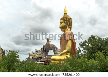 Golden Buddha statue in a Thai temple, The Temple in background have the form of an elephant. The name of this temple is Wat Ban Rai