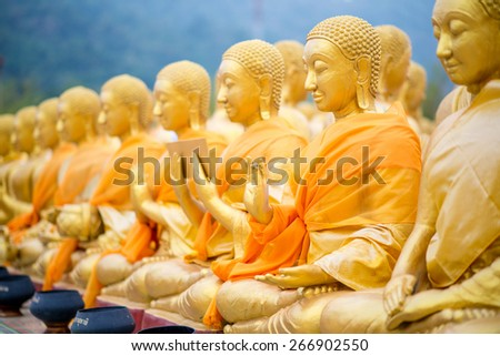 golden buddha statue in line - stock photo