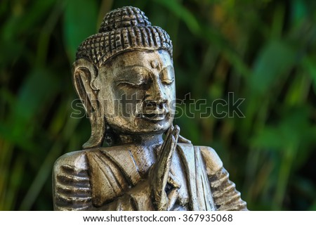 Golden Buddha statue meditating while making the symbolic Abhaya Mudra finger gesture. Right hand raised palm of the hand facing outward, fingers joined. Head/shoulders on background of green leaves. - stock photo