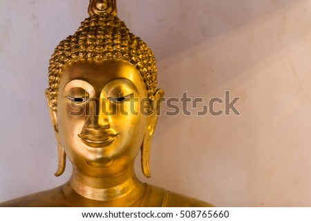 Golden Buddha statue with old temple wall background and sun light shade.