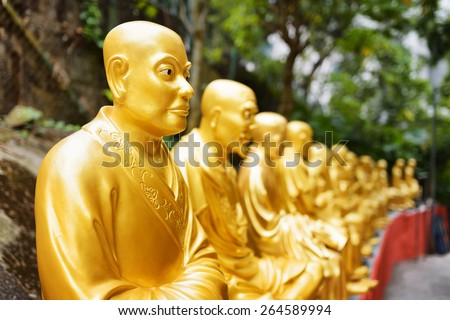 Golden Buddha statues along the stairs leading to the Ten Thousand Buddhas Monastery and landscape with green trees in the background in Hong Kong. Hong Kong is popular tourist destination of Asia. - stock photo