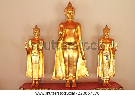 Golden Buddha statues on an alter - stock photo