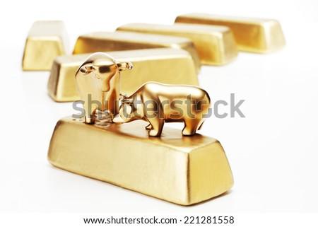 Golden bull bear figurine on gold bars - stock photo