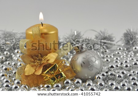 Golden burning candle and silver ball with Christmas decorations