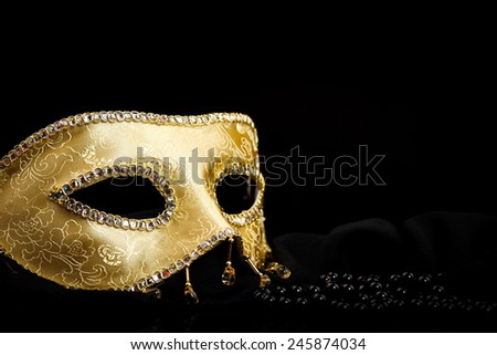 Golden carnival mask near pearls on black background - stock photo